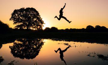 Una persona salta su uno specchio d'acqua