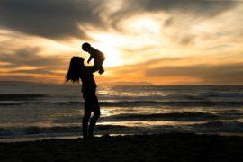 mamma con bambino in braccio al mare, sullo sfondo sole e nuvole scure